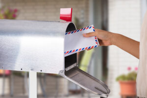 Person Removing Letter From Mailbox