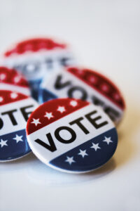 closeup of some vote badges for the United States election on an off-white background